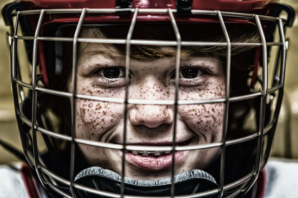 Freckle-faced child staring out of a hockey mask at the camera