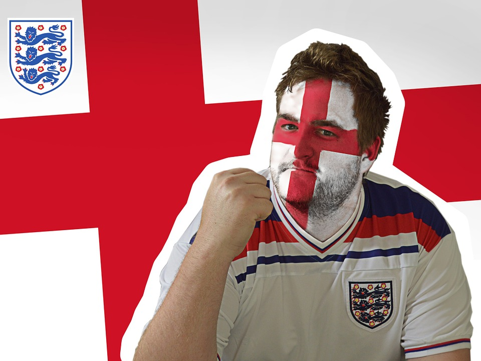 An england football fan wearing an England FC top & England flag facepaint with the english flag in the background