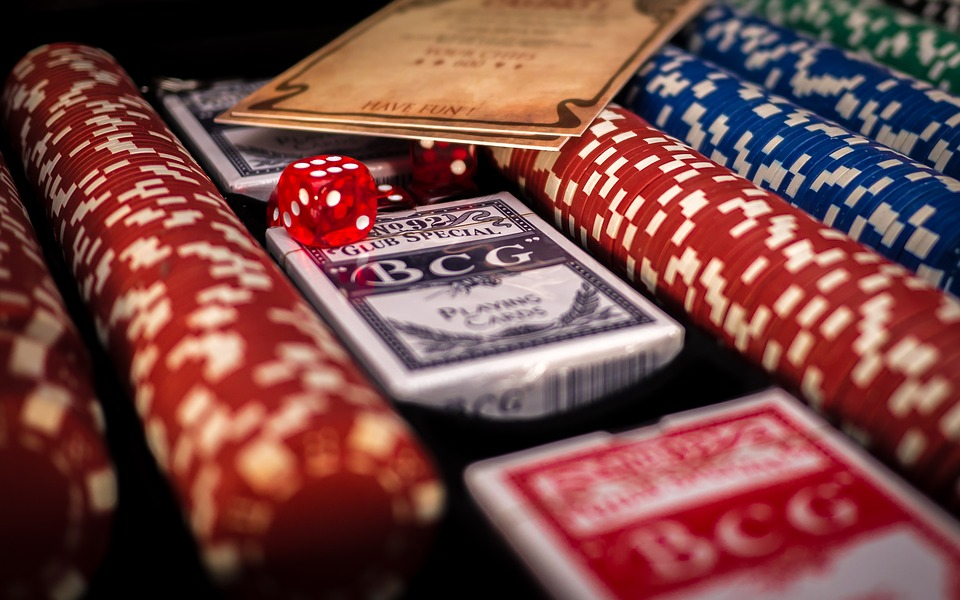 Poker chips, 3 decks of cards and a selection of dice all in a pile