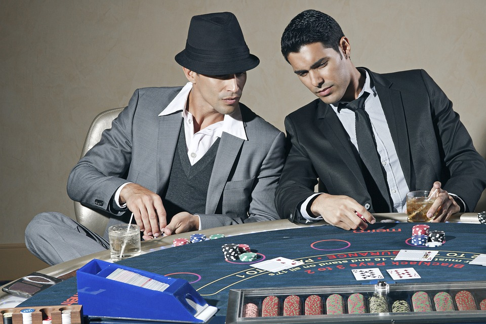 two men sitting around a poker table looking at the upturned cards on the table