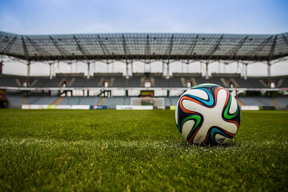 Football sitting on a grass pitch in the middle of an empty stadium facing goal