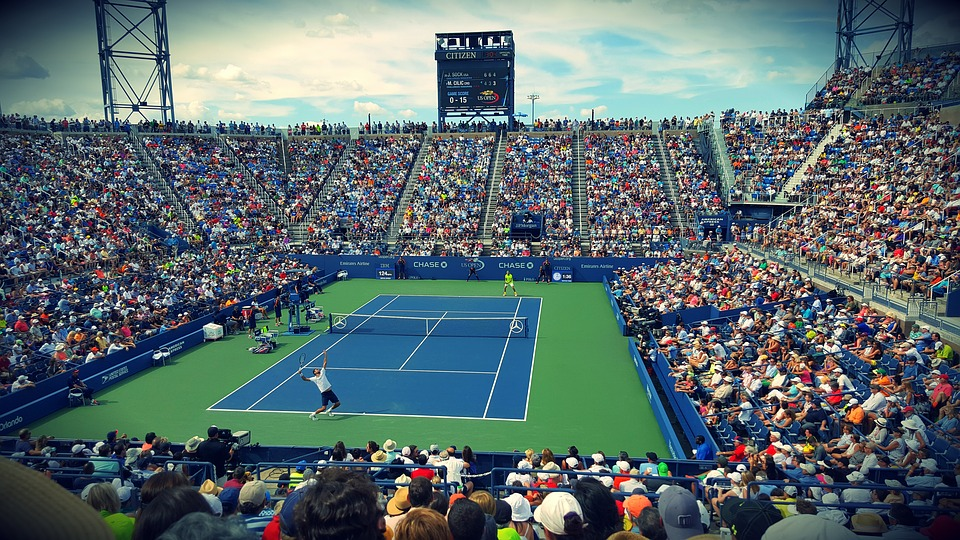 tennis court in a stadium with a crowd, tennis player about to serve