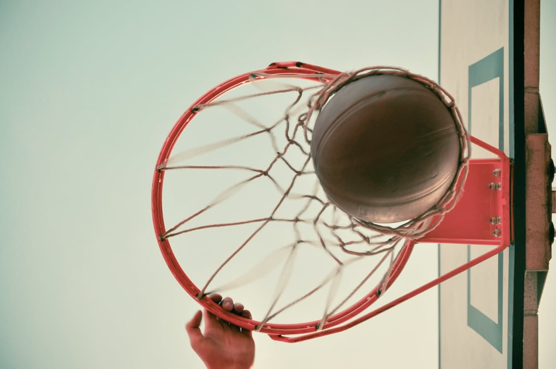 view from the bottom of a basketball hoop looking up, basketball coming through the hoop