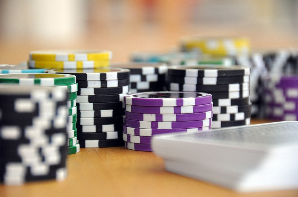 Piles of poker chips on a table with cards