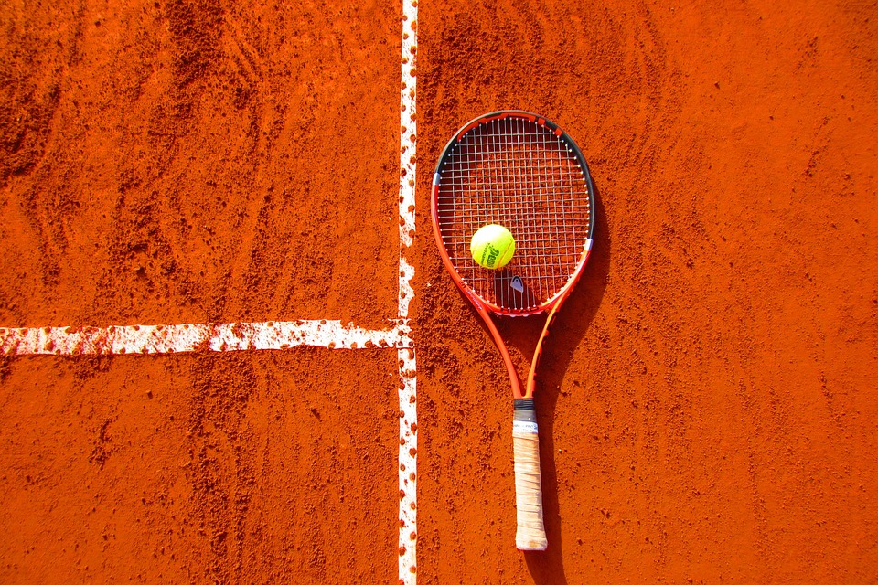 tennis racket & ball lying on sand covered tennis court